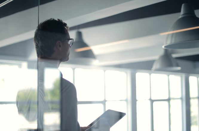 Man with tablet performing risk evaluation for a property in light-filled room.