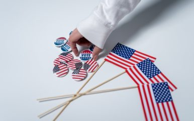 "An arm grabbing a ""vote"" pin on a table full of American flag pins and flags."